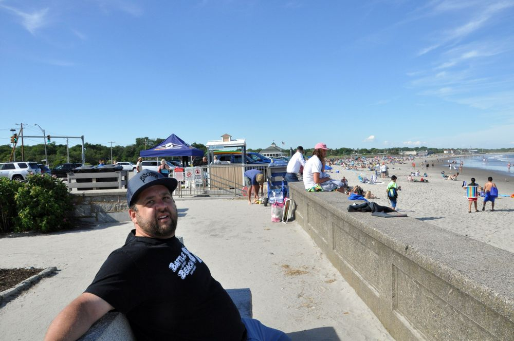 Conrad Ferla, a local surfer and advocate for shoreline access, sits along the seawall at the Narragansett Town Beach.