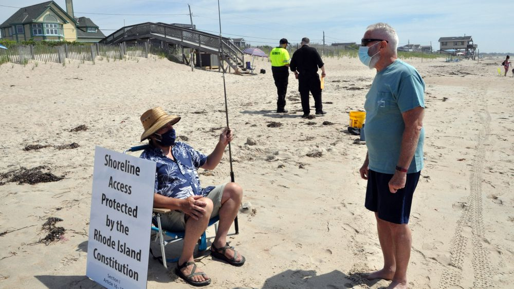 Scott Keeley, left, and Mark London, right, talk in South Kingstown on Saturday, June 27, 2020, just outside the Charlestown Town Beach limits. In the background, private security guards patrol the beach area.