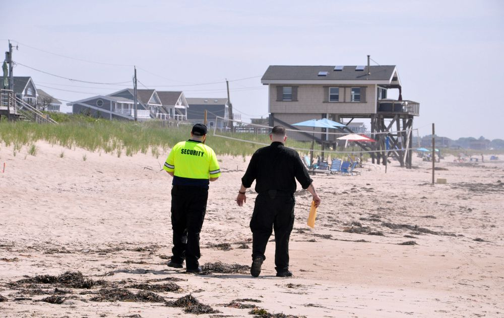 Private security guards walk the beach in South Kingstown.